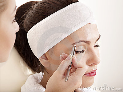 Tweezing eyebrow by beautician.