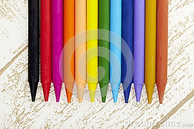 Twelve color pastel crayon  in box close up with woody texture backgrou