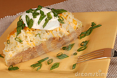Twice baked potato with scallions, cheese and sour cream
