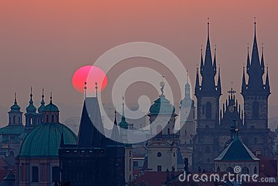 Twilight in historical city. Magical picture of tower with orange sun in Prague, Czech Republic, Europe. Beautiful detailed sunris Stock Photo
