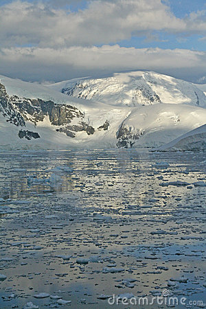 Twilight: Icy mountains reflected on calm sea