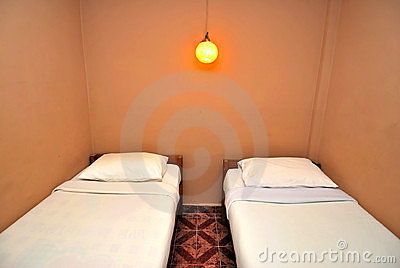 Twin beds in dark hotel room