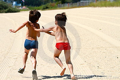 Twin boys play tag at the beach