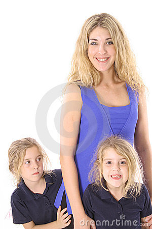 Twin daughter peeking around mother