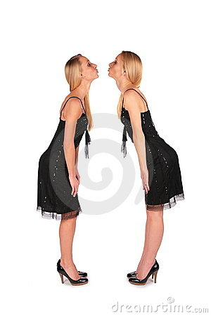Twin girls stands face-to-face kissing