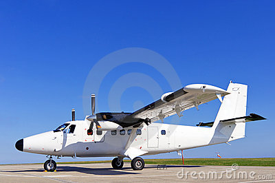 Twin propeller airplane on a runway.