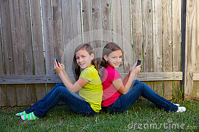 Twin sister girls playing smartphone sitting on backyard lawn