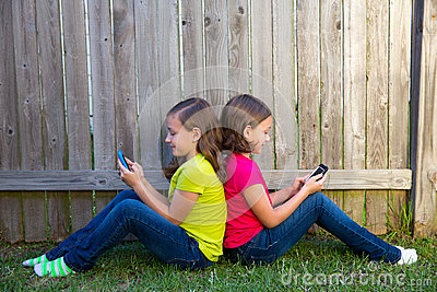 Twin sister girls playing smartphone sitting on backyard lawn