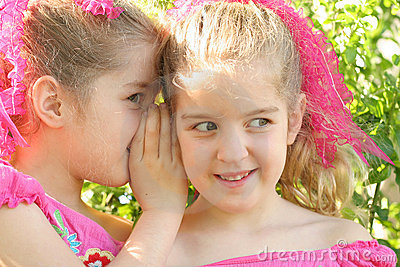 Twin sisters sharing a secret