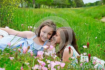 Twin sisters whispering ear on spring flowers meadow