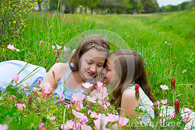 Twin sisters whispering ear on spring flowers meadow