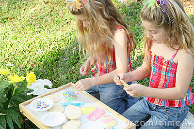 Twins decorating cookies outside