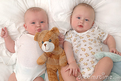Twins lying with their teddy bear