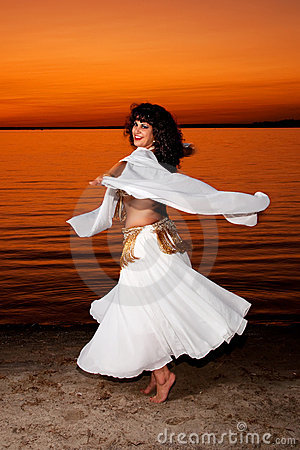 Twirling bellydancer at sunset
