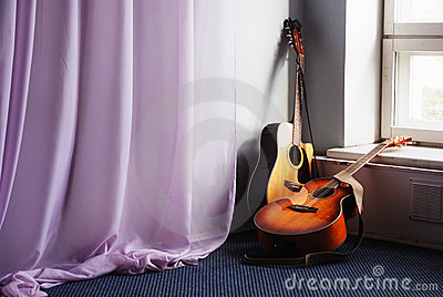 Two acoustic guitar next the window