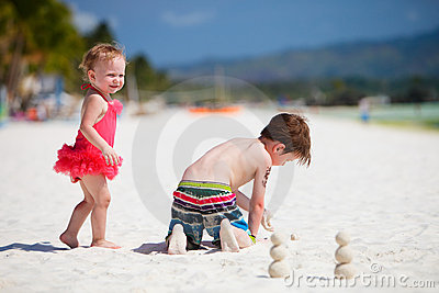 Two adorable kids standing by ocean shore