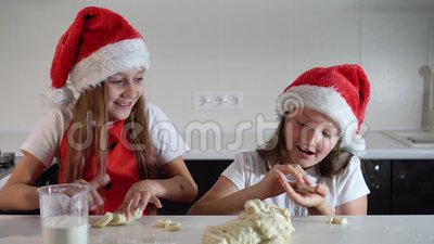 Two adorable little girls in santa claus hats and red christmas apron make cookies with their own hands. Smiling. happy new year a. Nd christmas stock footage