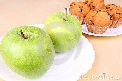 Two apples and cakes on white plates