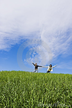 Two arms raised friends in a meadow