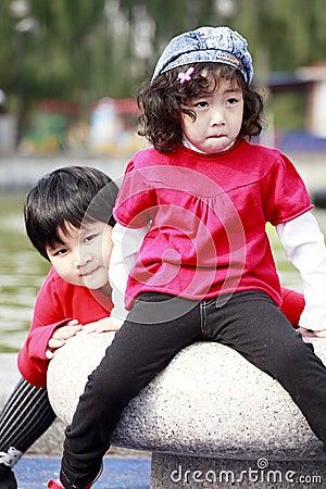 Two Asian little girls outdoors.