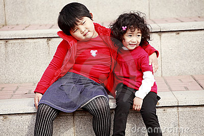 Two Asian little girls on stairs.