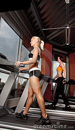 Two athletes doing exercise on treadmill