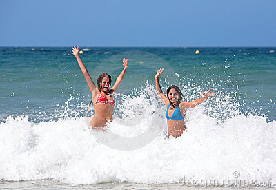 Two attractive young girl friends playing in the sea on vacation