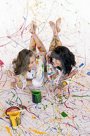 Two attractive young women covered in colorful paint