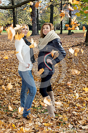 Two attractive young women posing with falling leaves