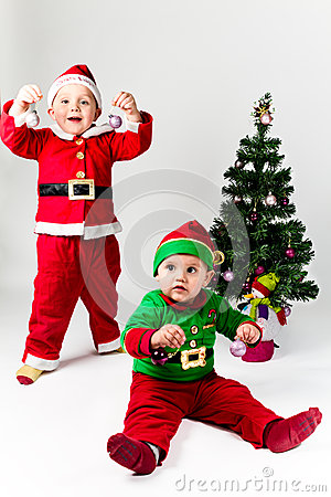 Two baby boys dressed as Santa Claus and Santa s Helper next to