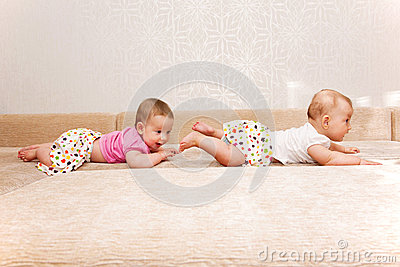 Two baby twins crawling one after another