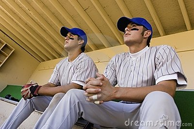 Two baseball team-mates sitting in dugout
