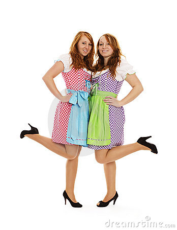 Two bavarian dressed girls lifting their feet