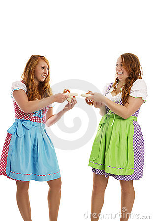 Two bavarian dressed girls pulling on veal sausage