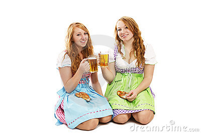 Two bavarian girls with pretzels and beer kneeling