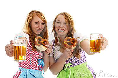 Two bavarian girls with pretzels cheering with bee