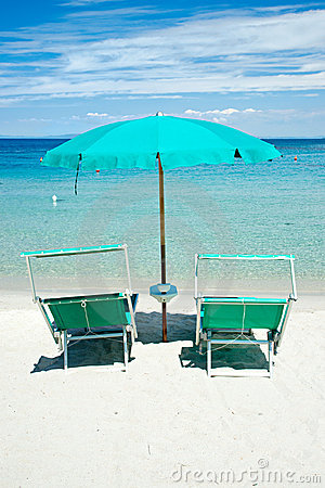 Two beach chairs with green umbrella.