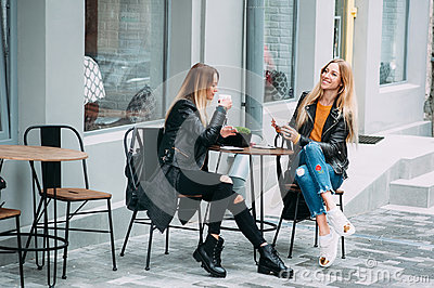 Two beautiful attractive stylish women are sitting outdoor in cafe drinking coffe and tea talking and enjoying great day. Stock Photo