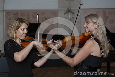 Two beautiful female violinists playing violin Stock Photo