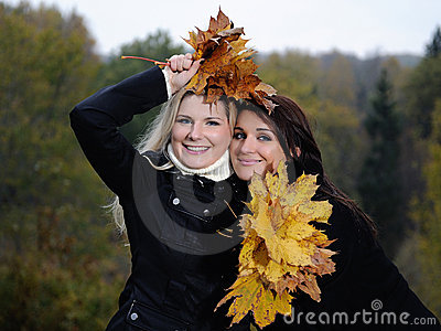 Two beautiful girl friends with autumn leafs