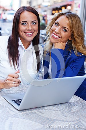Two beautiful girls in cafe with laptop