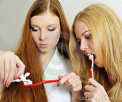 Two beautiful girls clean a teeth