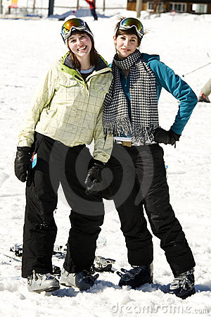 Two beautiful girls dressed in ski suits