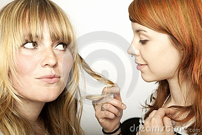 Two beautiful girls looking at hair