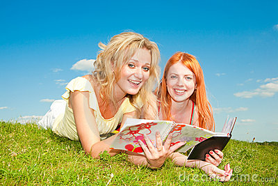 Two beautiful girls with notebooks outdoors