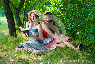 Two Beautiful happy smiling young women reading