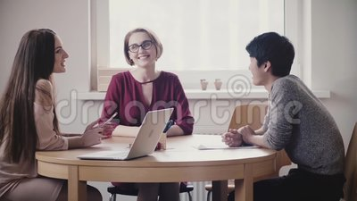 Two beautiful positive Caucasian girls talk to Japanese man at a job interview by the table in modern healthy office. Young company managers discuss future stock video