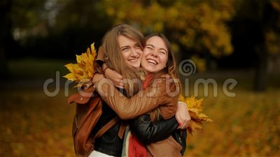 Two Beautiful Teenage Girls Hugging and Holding a Bouquet of Yellow Leaves in the Autumn Park, Girlfriends Having Fun in. Outdoor HD stock video