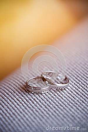 Two beautiful white gold engagement rings with diamond stones lie on the fabric with a rough texture. Wedding ring Stock Photo