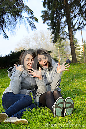 Two beautiful woman expressing excitement in a park